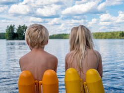 Young boy and girl child sits on a dock near the lake. They are wearing swimming ring to bathe safe in the water. View from back.