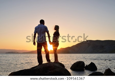 Young boy and girl look at each other, hand in hand on the beach at sunset