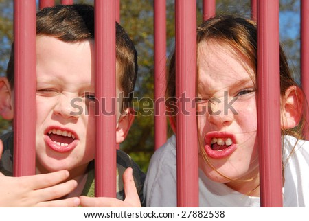 young boy and girl making silly faces on playground toy