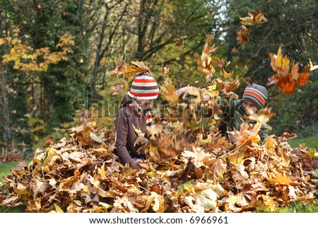 Young boy and girl playing in pile of leaves