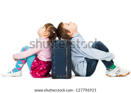 Young boy and girl sitting back to back against a suitcase their eyes shut  with  tiredness and boredom.