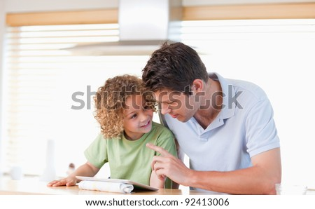 Young boy and his father using a tablet computer in their kitchen