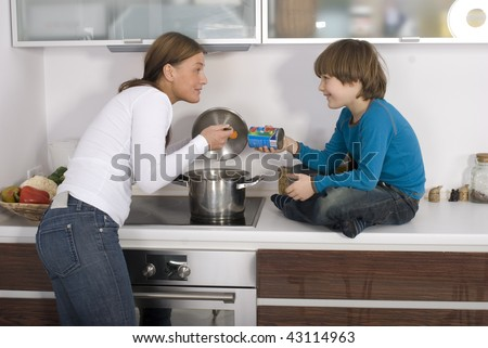 Young boy and his mother are standing over the stove cooking dinner.