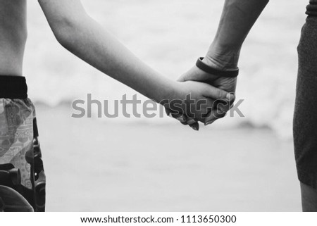 Young boy and his mother holding hands on the beach walking towards the ocean water. #1113650300
