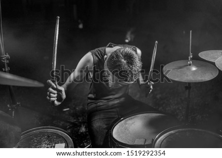 young boy as talented rock band drummer . Handsome and cool Asian American teenager in headband playing drum kit performing night music show as hobby in teenage  love for music