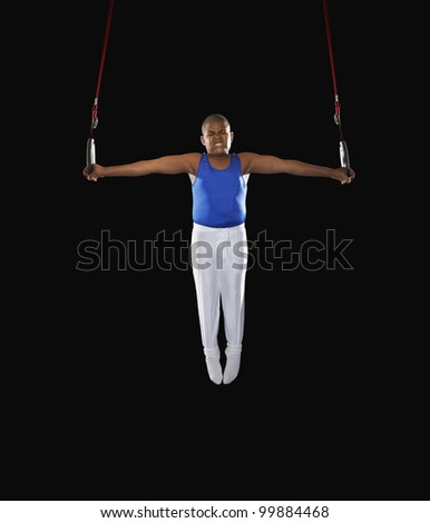 Young boy balancing on the gymnastic rings