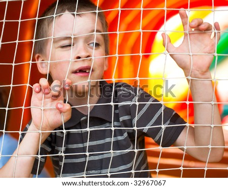 Young boy behing the net at playground