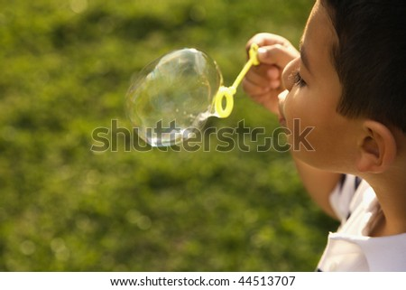 Young boy blowing bubbles outside. Horizontally framed shot.