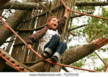 Young boy calling while climbing high tree and ropes