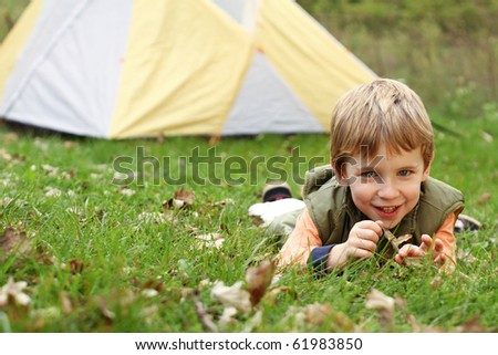 Young boy camping with tent