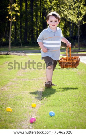 Young boy chases after eggs in easter egg hunt.
