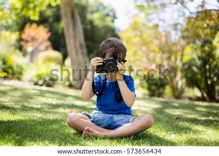 Young boy clicking a photograph from camera in park