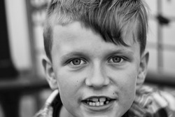 Young boy close up of face. Photograph black and white. Mouth open, big eyes.
