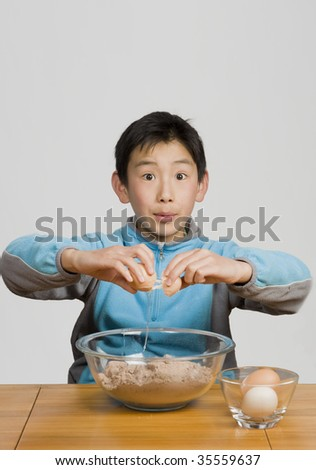 young boy cracking egg into bowl
