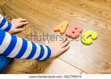 young boy demonstrating his collection of capital letters while sitting on brown wooden floor #361798475