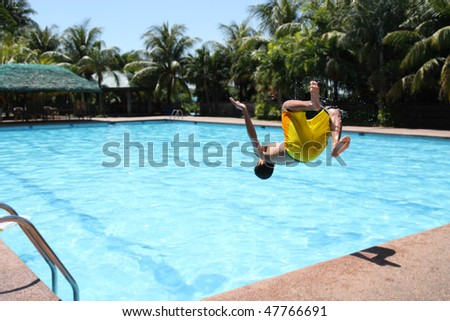 young boy diving on a swimming pool
