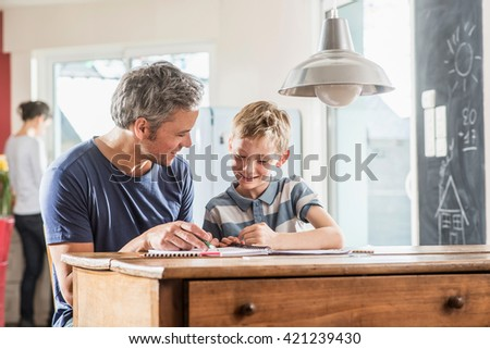 Young boy doing his school homework with his father, the boy is writing in his book, at the blurred background the mother works in the kitchen