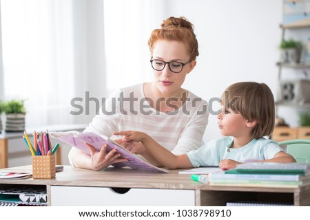 Young boy doing homework during extra-curricular classes with a tutor