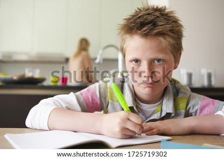 Young boy doing homework, mother in kitchen in background