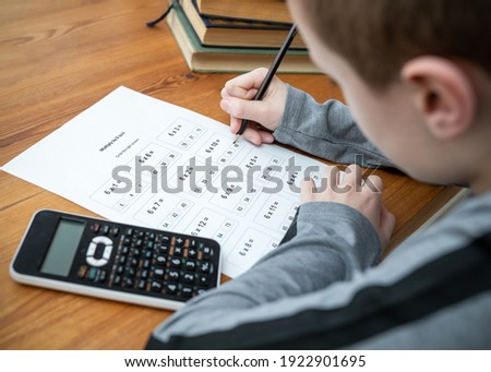 Young boy doing maths homework test times tables multiplication exam paper sat at table homeschooling education with calculator and books holding pencil learning mathematics  getting answers right Stok fotoğraf ©