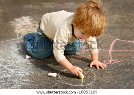 Young boy drawing outside with chalk