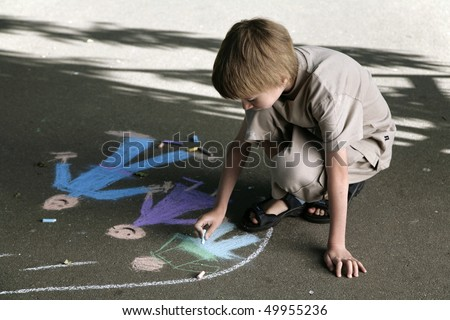 young boy draws the bright pieces of chalk on sidewalk - stock photo