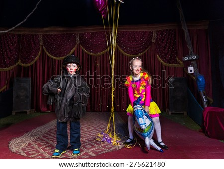 Young Boy Dressed as Clown Standing on Stage with Girl in Vibrant Costume Holding Horse Shaped Balloon