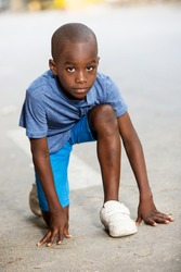 young boy dressed in T-shirt ready to run.