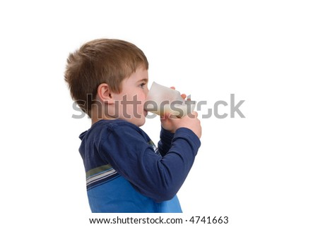 Young boy drinking a glass of milk, isolated on white with copy space