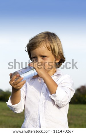 Young boy drinking water whilst playing outdoors on the grass