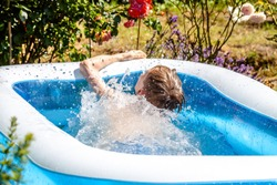 Young boy drowning in the swimming pool in the summer.