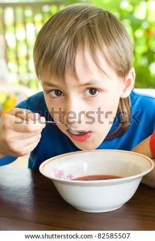 young boy eating a soup at table