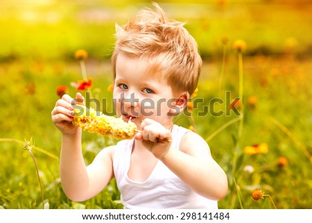 Young boy eating an ear of grilled corn on the cob