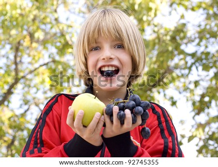 young boy eating fruit - stock photo