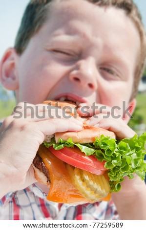 Young boy eating huge burger at cookcout