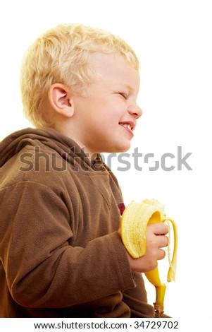 Young boy eats a banana - stock photo