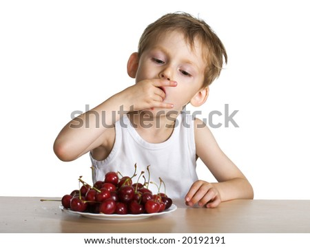 Young boy eats a cherry