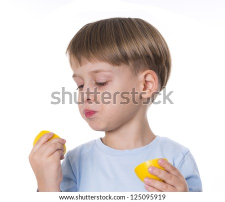 young boy eats lemon