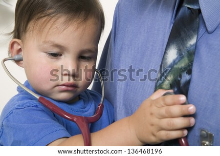 Young boy examining his father with stethoscope