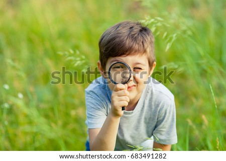 Young boy exploring nature in the meadow with a magnifying glass looking at flowers. Curious children in the woods, a future botanist.  Stock photo ©