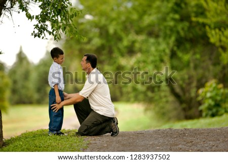 Young boy facing his kneeling father.