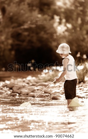 young boy fishing alone in a river, nostalgic aged sepia tone