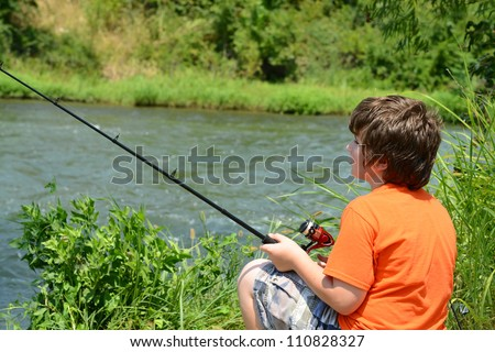 Young boy fishing in a river