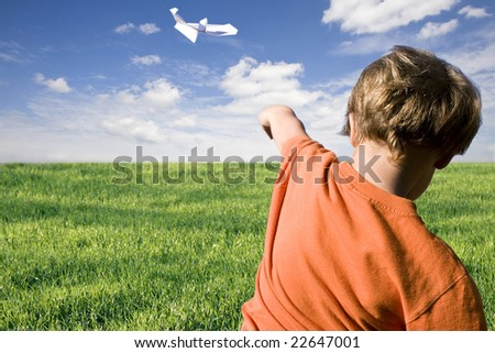young boy flying a paper airplane