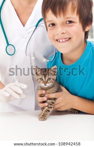 Young boy getting his small kitten to vaccination at the veterinary - focus on the cat