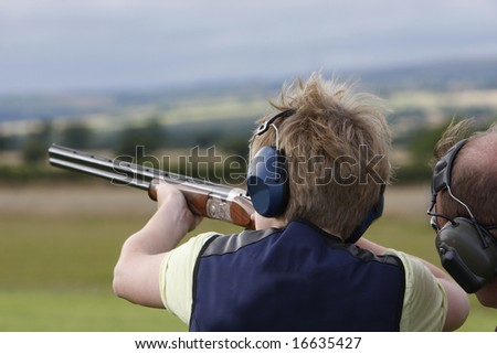 Young boy given advice on  clay pigeon shooting