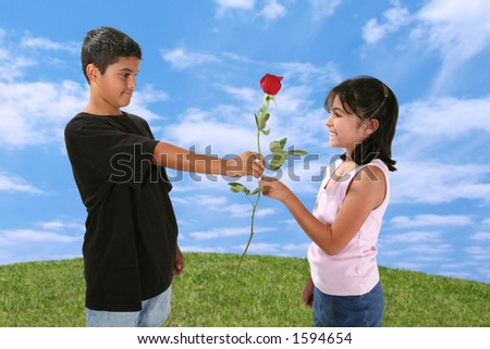 Young boy giving a young girl a red rose