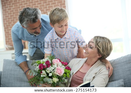 Young boy giving flowers to mommy for mother\'s day