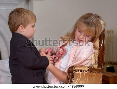Young boy giving flowers to sleeping girl