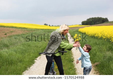 Young boy giving mother on bicycle yellow flowers
